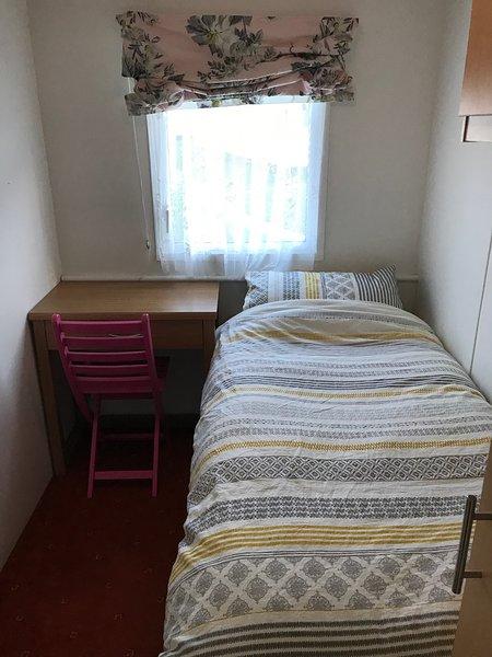 La chambre simple a une taille complète lit simple avec bureau, une chaise, une armoire et placards