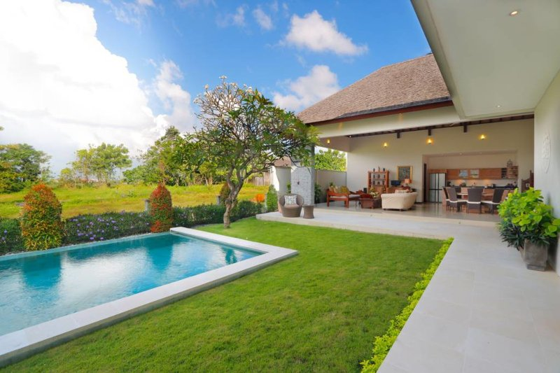 the living room is an open area facing the pool and garden