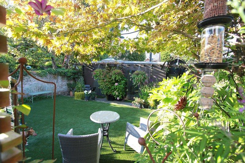 Ospite privato uso di terrazza inferiore e prato con tavolo da bistrò e sedie