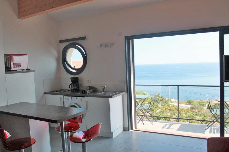 salón y cocina con vista al mar