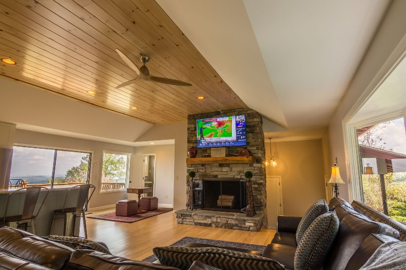 The great room with wood burning fireplace with TV and sectional sofa