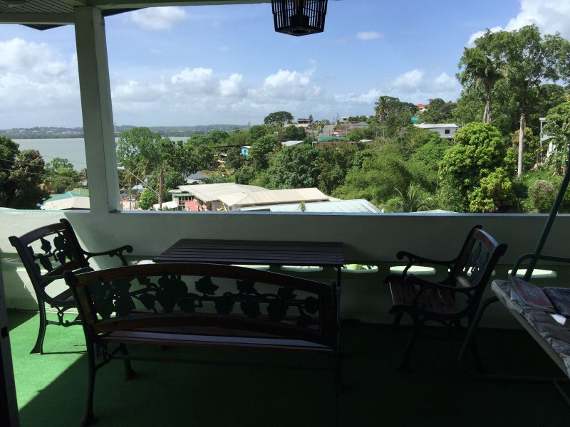 Beautiful view of the gulf of Paria in a cossy gallery setting with picnic table and  lovers swing..