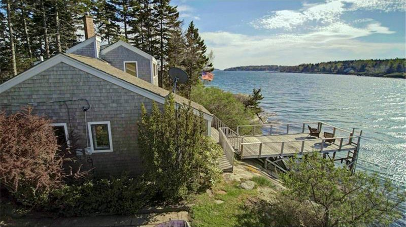 Side of cottage with view of deck and water