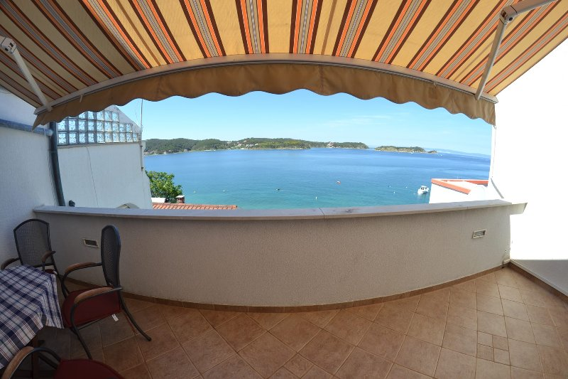 Balcone con tenda da sole e vista diretta sul mare