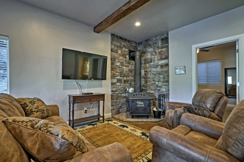 The open-concept living space features a rustic charm with a wood-burning stove.