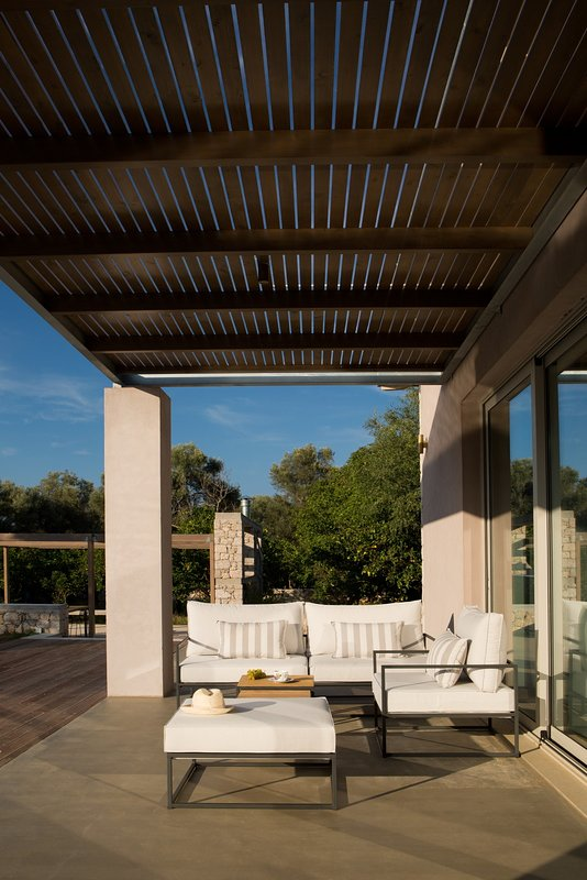 The sitting area in front of the livingroom under the shadow of the pergola