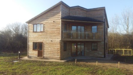 Wood cladding over a well insulated building designed to fit a woodland landscape