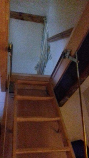 Peldaños de la escalera plegable en Loft dormitorio. puerta de seguridad anteriormente.