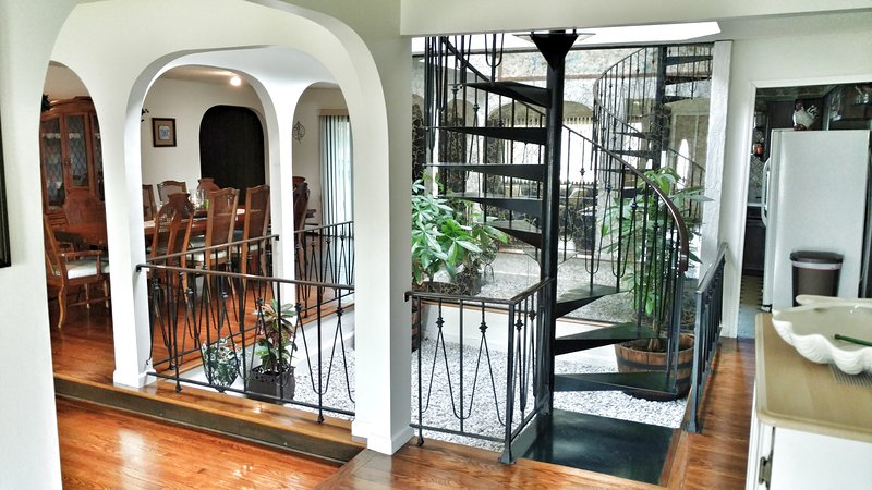 View of indoor garden, spiral staircase from foyer
