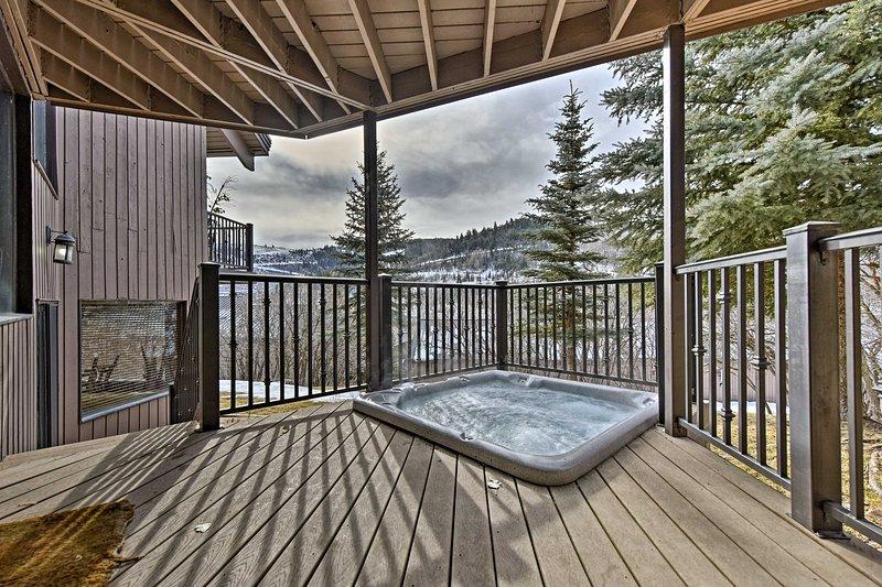Le bain à remous intégré privé est encadré par des vues spectaculaires sur les montagnes.