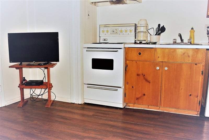 Kitchenette with a fridge, stove, coffee maker, sink and microwave