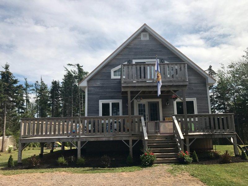 Frente de casa de campo con gran envoltura alrededor de la cubierta y la cubierta en el dormitorio principal privado.
