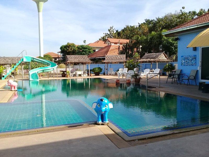 La vue depuis l'entrée de la piscine tropicale. (Piscine, cabanes avec sièges, chaises longues et curseur)