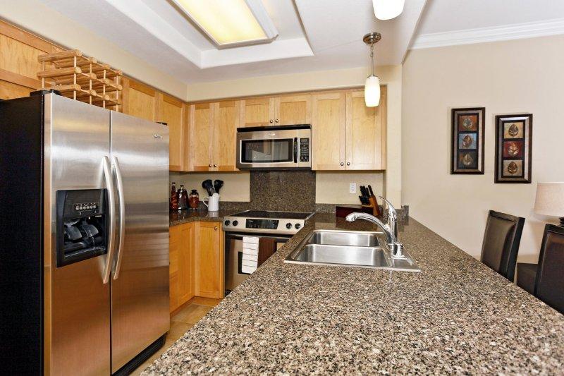Cocina con electrodomésticos de acero inoxidable y encimera de granito