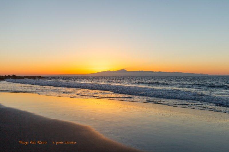puesta de sol en la playa de El Risco, isla de Tenerife en el horizonte