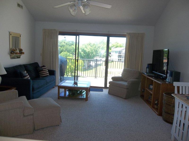 salon spacieux avec plafond voûté et un ventilateur de plafond