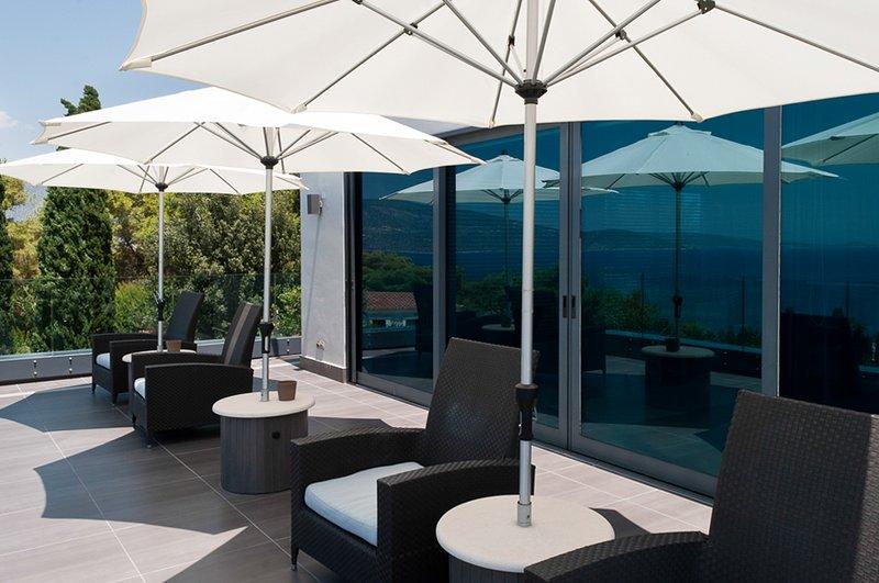 Sillas acogedoras con vistas al mar y impresionante puesta de sol en la galería balcón de la planta