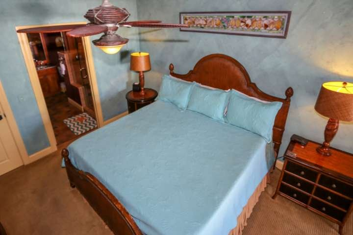 The master bedroom has a king sized bed, carpeted floors and ceiling fan.