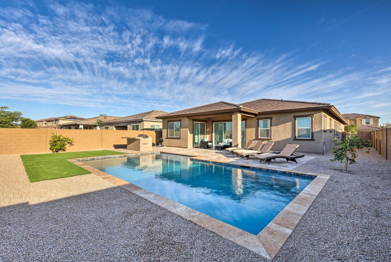 This Litchfield Park home offers a pool, grilling area & cushioned lounge chairs