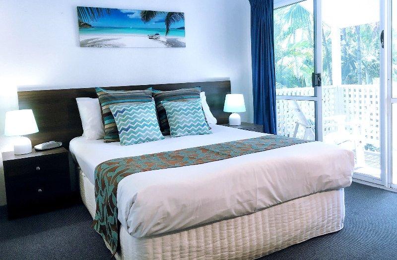Bedroom with Queen Bed, opens onto Full Length Balcony overlooking pool