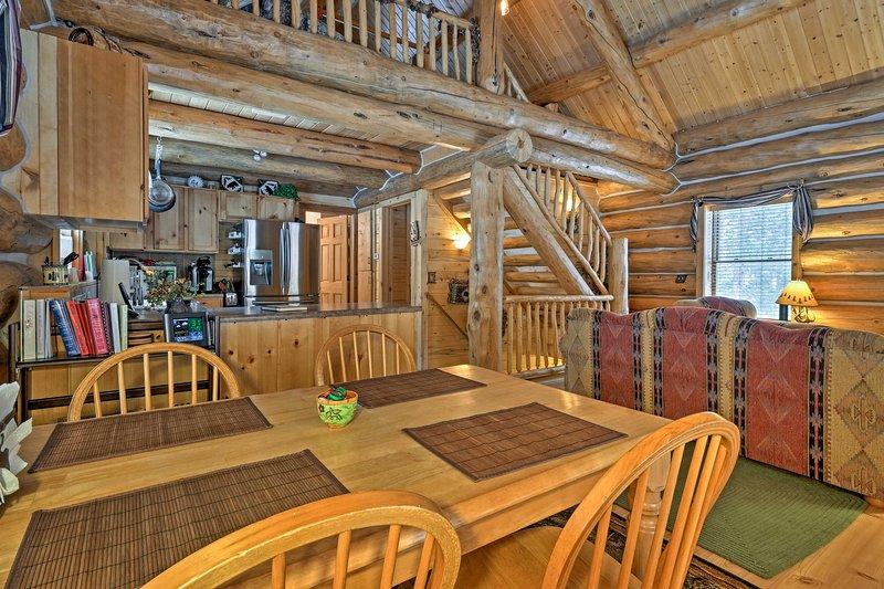 1470 pieds carrés d'espace de vie est encadrée par des poutres en bois et des structures de logarithme naturel.