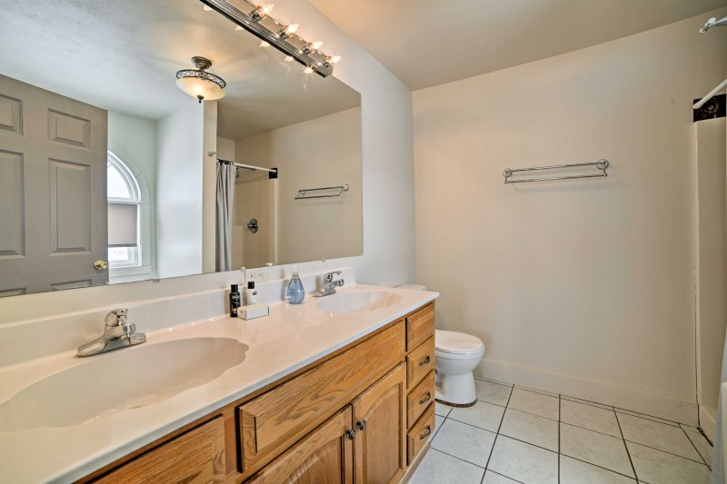 The en-suite bathroom is equipped with a tub, walk-in shower and his-and-hers vanity.