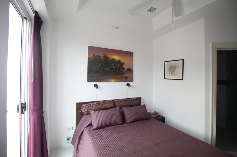 Second bedroom with queen size bed, private bathroom and balcony.