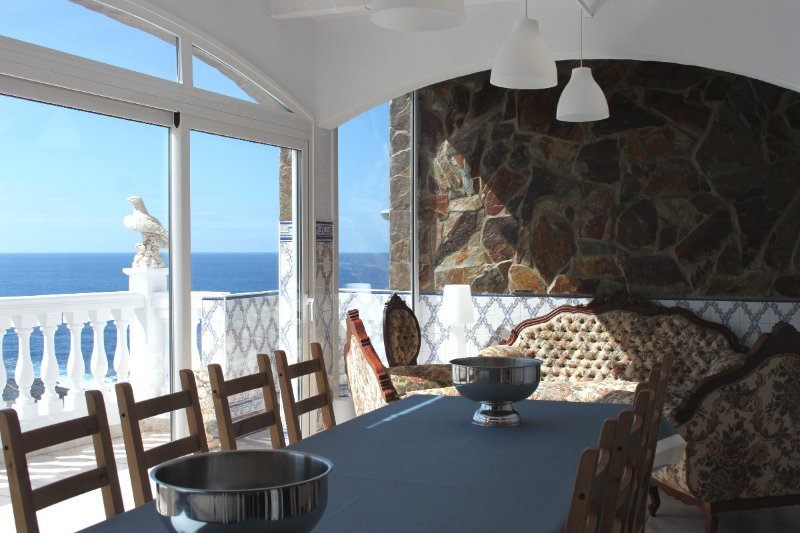 Dining room with a large bay that opens onto the balcony and ocean