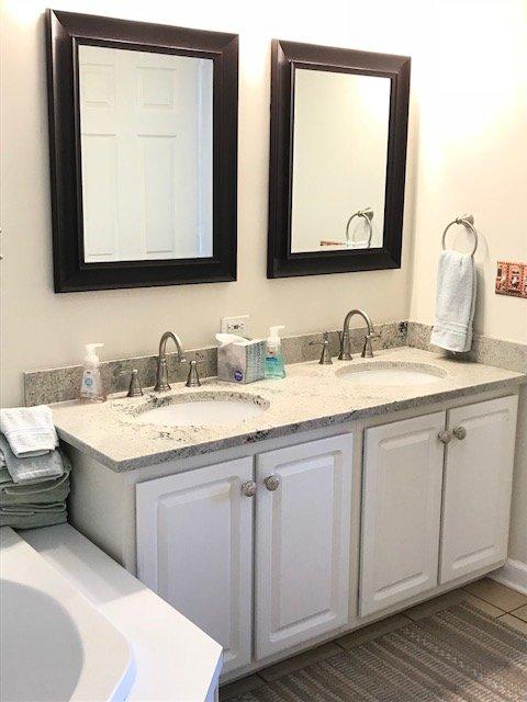 Master bain avec deux lavabos dans de nouveaux comptoirs en granit avec douche et baignoire jacuzzi séparés