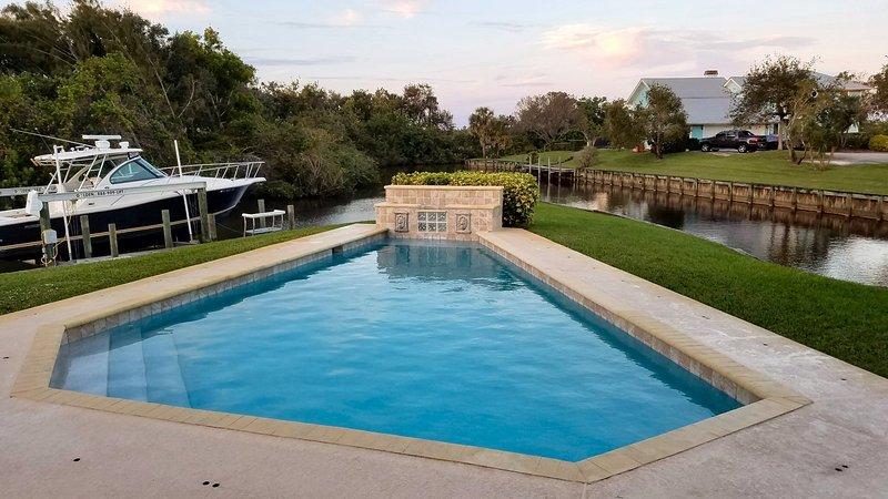 Gran piscina construida en el punto con agua y naturaleza a su alrededor.