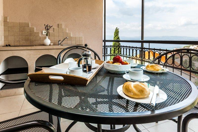 espaçoso terraço com mesa de jantar e cozinha externa