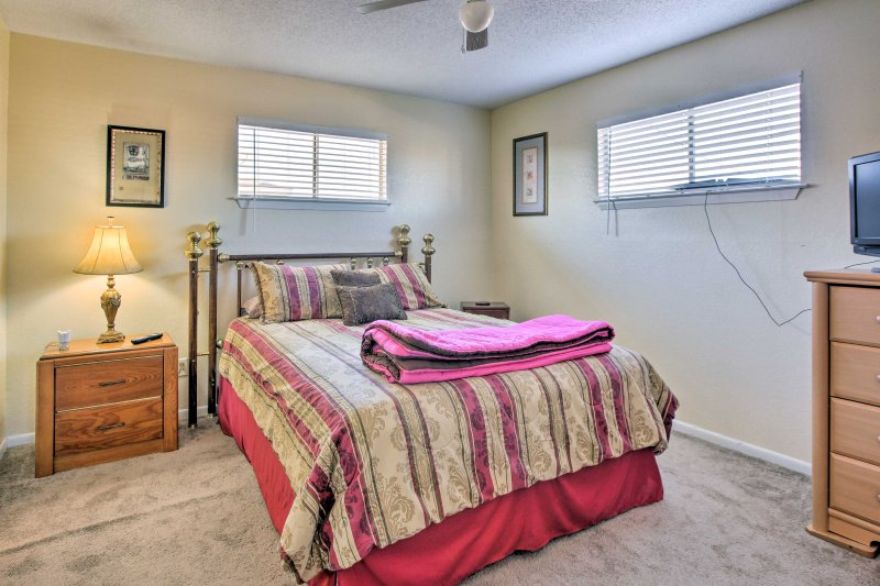 This bedroom features a queen bed and flat-screen TV.