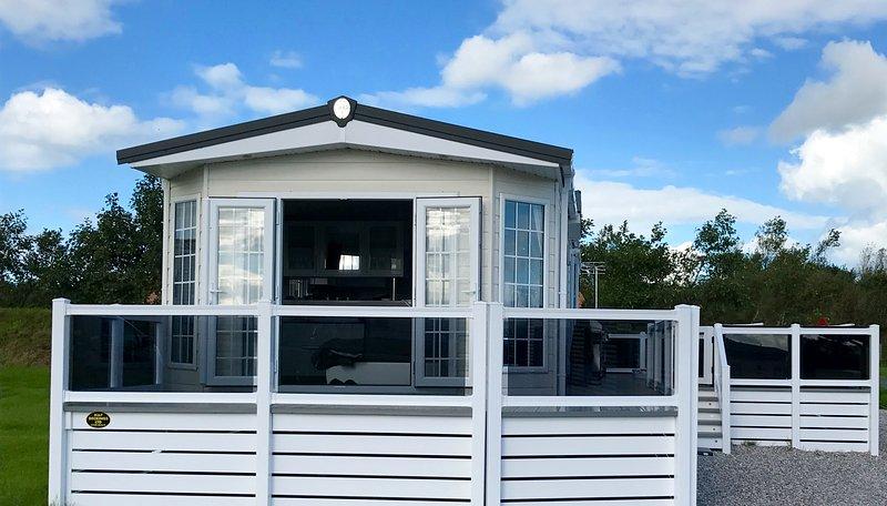 terraza delantera con 2 sillas de mimbre y una mesa para tomar el sol de la mañana con una taza de café.