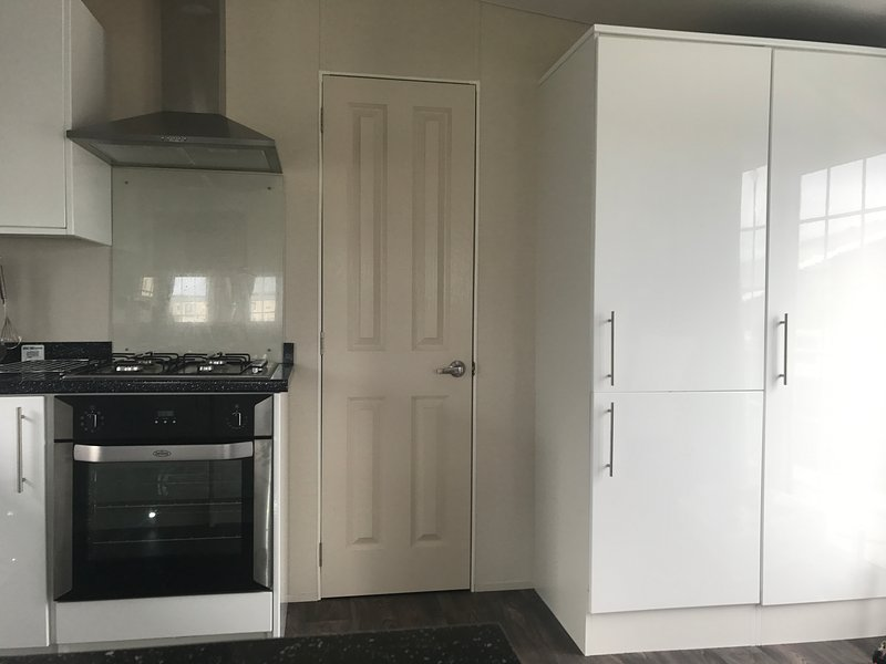 Electric cooker and gas hob, full size fridge and freezer.