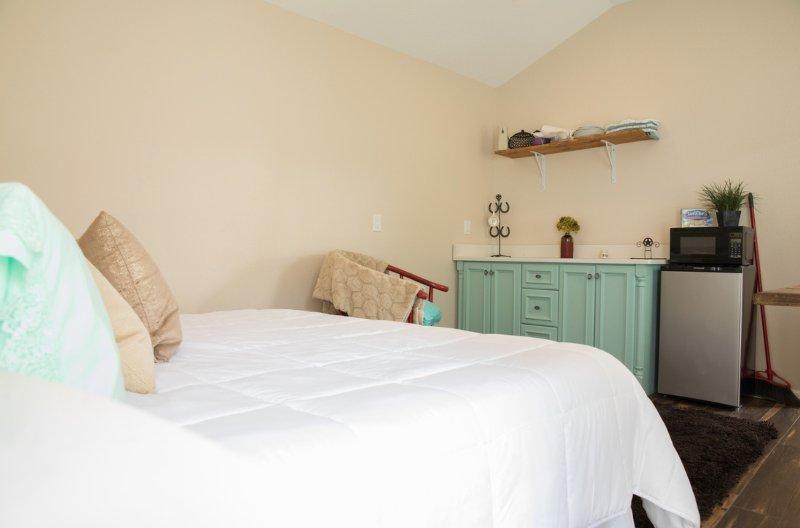 Dormitorio encantador con microondas, nevera y cafetera
