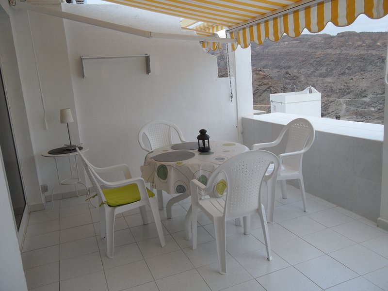 terrace with canopy, dining table, chairs,  small table with lamp