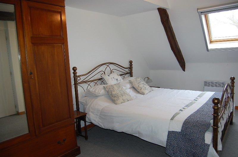 El dormitorio principal tiene una muy cómoda cama king size de latón