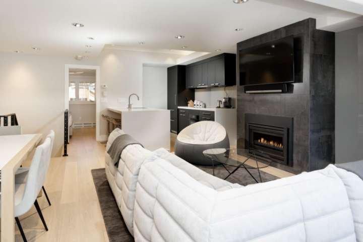 La sala de estar concepto abierto con TV de pantalla plana con Sonos, una chimenea de gas, mobiliario de diseño y una cocina de lujo