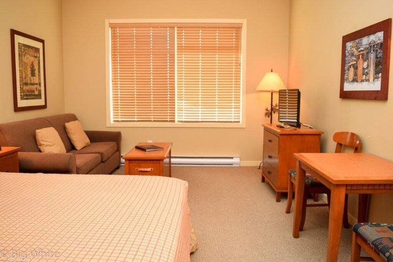 The suite features a sofa, TV and dining table.