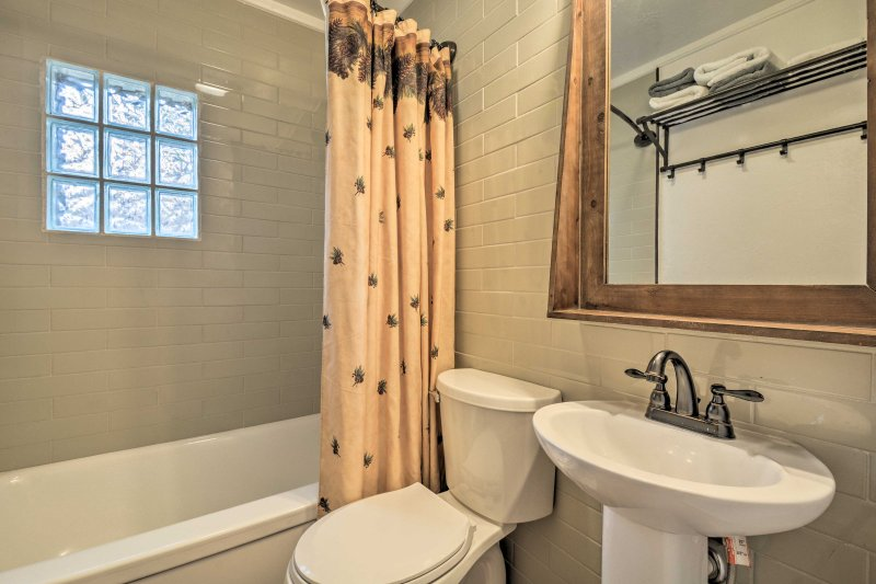 Freshen up using the shower/tub combo in the bathroom.