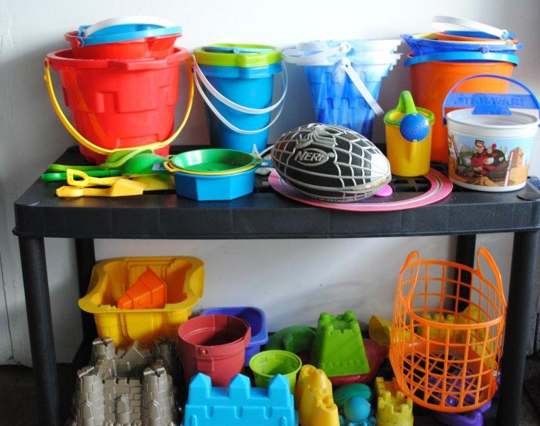 giocattoli di sabbia pronti per la spiaggia, insieme a una borsa da spiaggia e da bagno