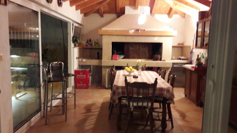 Grand barbecue avec coin salon et salle à manger, près de la piscine et de jacuzzi.