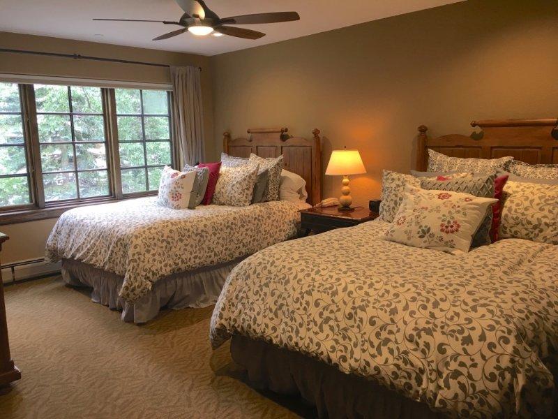 Slaapkamer met twee hemelse queen bedden.