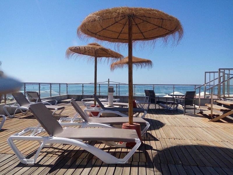 Liegestühle und Sonnenschirme Kilometer Strand auf der ersten Linie mit Blick auf