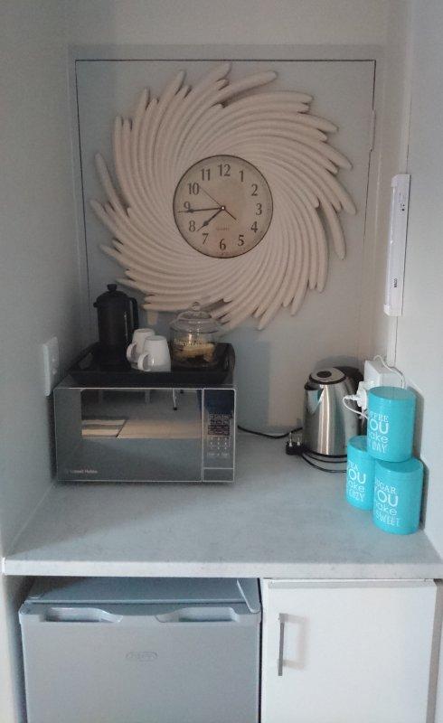 angolo cottura con stoviglie, forno a microonde, bollitore e frigo