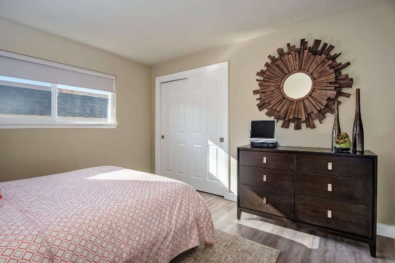 The first bedroom also includes a closet, dresser, and a drawer at the foot of the bed.
