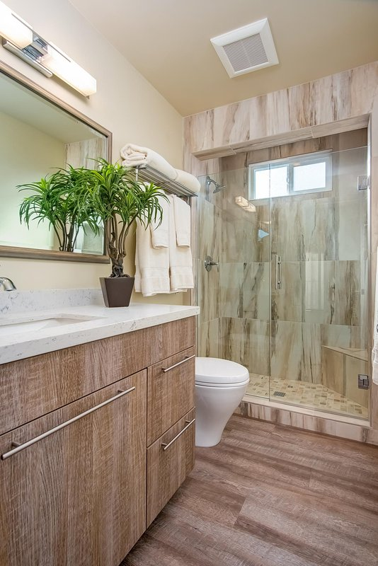 The bathroom is gorgeously remodeled and includes a shower.