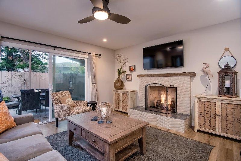Unité A: Salon avec TV, cheminée et portes donnant sur un patio privé