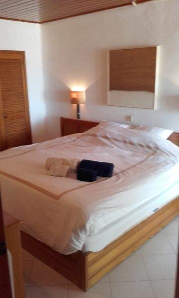 Super king-size bed in de slaapkamer met openslaande deuren naar balkon en uitzicht op zee