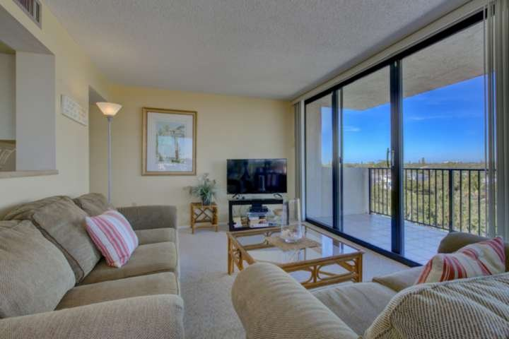 Living room with sliding door to balcony.  Enjoy being entertained by the large flatscreen TV.